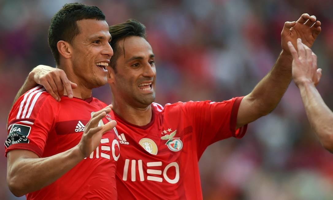 Em Portugal, Rodrigo Lima e Jonas comemoram um dos gols do Benfica nos 3 a 1 sobre o Nacional FRANCISCO LEONG / AFP