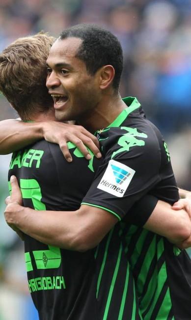 O brasileiro Raffael, à direita, que já havia marcado duas vezes contra o Bayern de Munique, é abraçado ao fazer mais um gol em nova vitória do Borussia Moenchengladbach DANIEL ROLAND / AFP