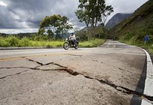 Pavimento comprometido: Motoqueiro passa pelo km 14 da BR-495, na Região Serrana do Rio: concreto da pista está rachado e erosão se estende pela pista Foto: Agência O Globo / Márcia Folheto
