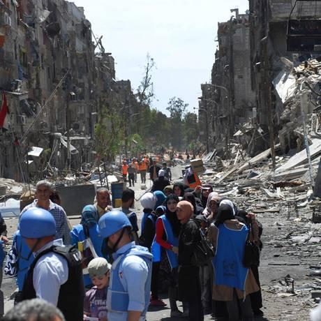 Foto da agência humanitária da ONU em abril de 2014 mostra trabalho e Yarmouk, com vários prédios destruídos após bombardeios Foto: UNRWA / AP
