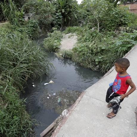 Criança observa esgoto a céu aberto Foto: Domingos Peixoto / Agência O Globo