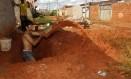 Observado pelo tio Francisco Rodrigues, Francisco Viana cava uma fossa para a casa onde vive Foto: Agência O GLOBO / Jorge William