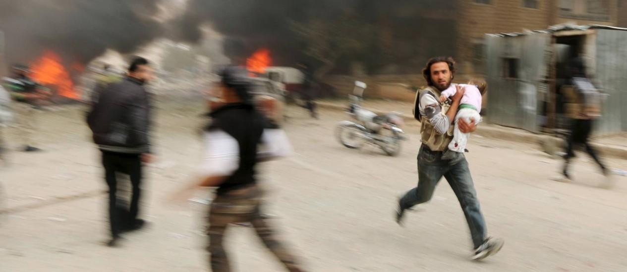 Homem corre com criança ferida durante confrontos em Idlib Foto: AMMAR ABDALLAH / REUTERS