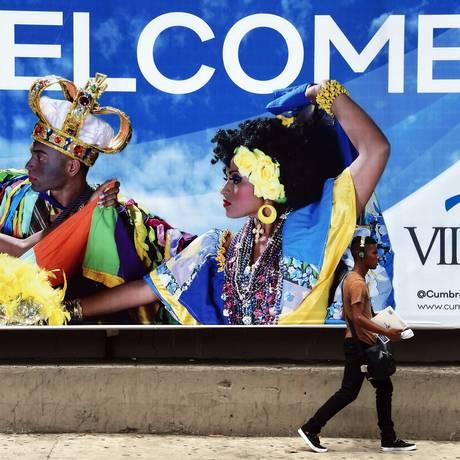 Homem passa por cartaz da Cúpula das Américas, que começa na sexta-feira, no Panamá Foto: RODRIGO ARANGUA / AFP