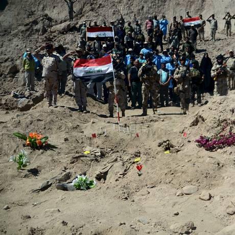 Soldados iraquianos prestam homenagem aos mortos no local onde os corpos foram encontrados Foto: STRINGER / REUTERS