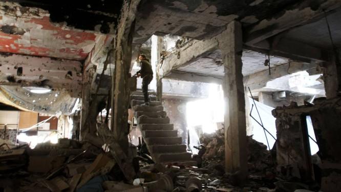 Um homem sobe as escadas de um edifício destruído no campo de Yarmouk Foto: YOUSSEF KARWASHAN / AFP