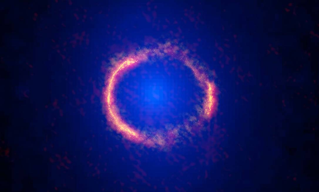 Composição de observações feitas pelos telescópios Alma e Hubble mostra a galáxia SDP.81, localizada a 12 bilhões de anos-luz da Terra, cuja imagem deformada pelo fenômeno de lente gravitacional de outra mais próxima a ponto de ficar com a aparência de um anel, como previsto pela Teoria da Relatividade Geral de Albert Einstein Foto: / Alma (NRAO/ESO/NAOJ)/Hubble (Nasa/ESA)