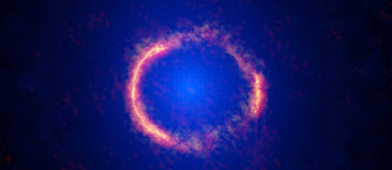 Composição de observações feitas pelos telescópios Alma e Hubble mostra a galáxia SDP.81, localizada a 12 bilhões de anos-luz da Terra, cuja imagem deformada pelo fenômeno de lente gravitacional de outra mais próxima a ponto de ficar com a aparência de um anel, como previsto pela Teoria da Relatividade Geral de Albert Einstein Foto: Alma (NRAO/ESO/NAOJ)/Hubble (Nasa/ESA)