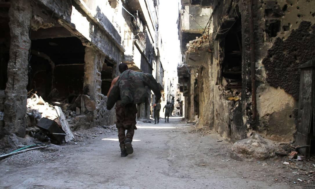 Homem caminha por prédios destruídos no campo de refugiados palestinos Yarmouk, próximo à capital síria, Damasco Foto: YOUSSEF KARWASHAN / AFP