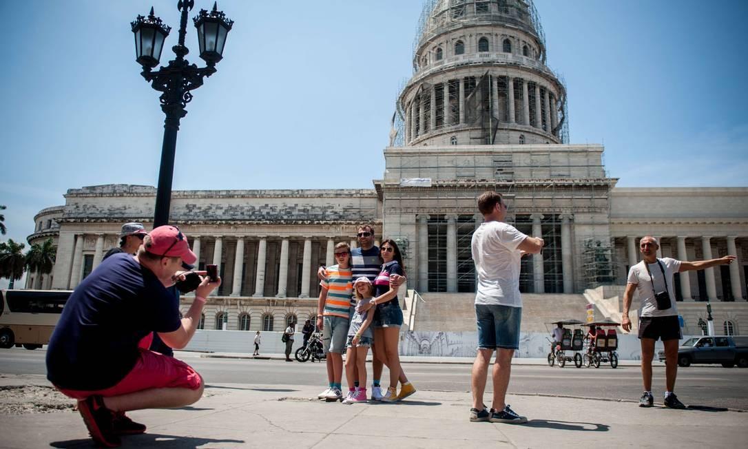 Mercado em expansão. Americanos posam em frente ao Capitólio, em Havana: cidade já ultrapassou destinos tradicionais na América do Sul, como Rio e Buenos Aires Foto: / YAMIL LAGE/AFP