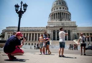 Mercado em expansão. Americanos posam em frente ao Capitólio, em Havana: cidade já ultrapassou destinos tradicionais na América do Sul, como Rio e Buenos Aires Foto: YAMIL LAGE/AFP