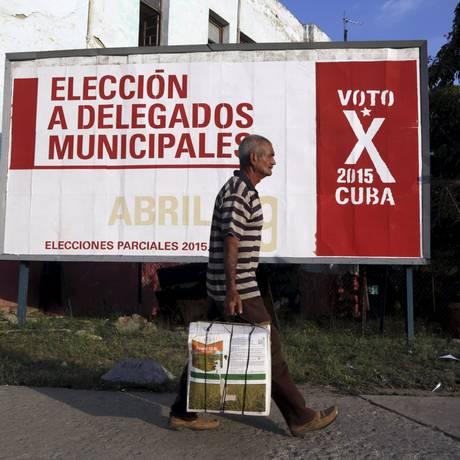 Um homem passa por um outdoor em Havana anunciando as eleições municipais cubanas: dois dissidentes dizem ter tido suas biografias aletradas Foto: ENRIQUE DE LA OSA / REUTERS