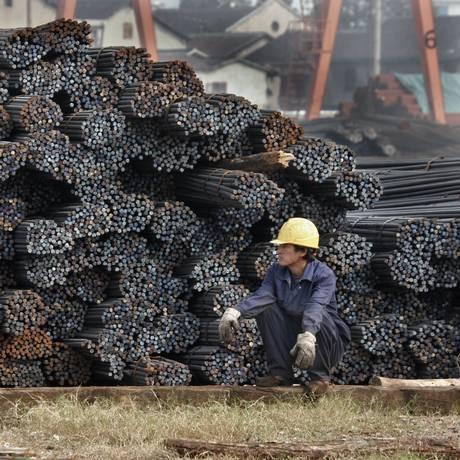 Trabalhador ao lado de pilhas de hastes de aço de construção em um mercado de produtos de aço em Xangai, na China Foto: Bloomberg News