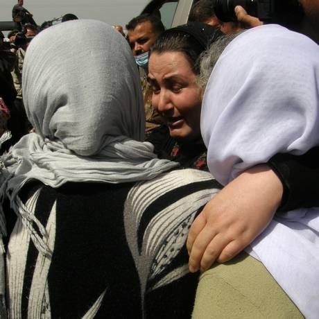 Mulheres yazidis libertadas pelo Estado Islâmico se abraçam ao chegarem a Kirkuk. Grupo liberou mais de 200 reféns, em sua maioria crianças e idosos Foto: Uncredited / AP