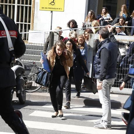 Um policial ajuda a retirar as pessoas do Palácio da Justiça de Milão Foto: Luca Bruno / AP