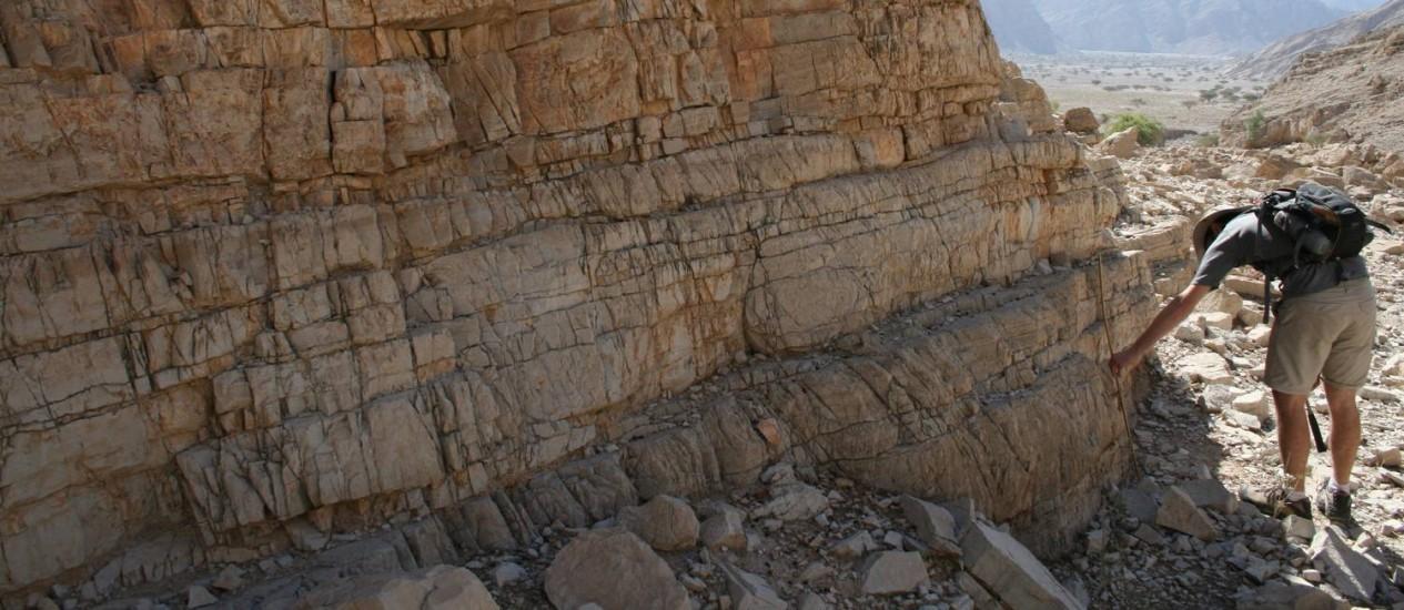 Pesquisador junto a uma das formações calcárias nos Emirados Árabes Unidos de onde os cientistas retiraram amostras de rochas para montar registro do processo de acidificação dos oceanos entre o fim do Permiano e início do Triássico Foto: Divulgação/Science/Matthew Clarkson