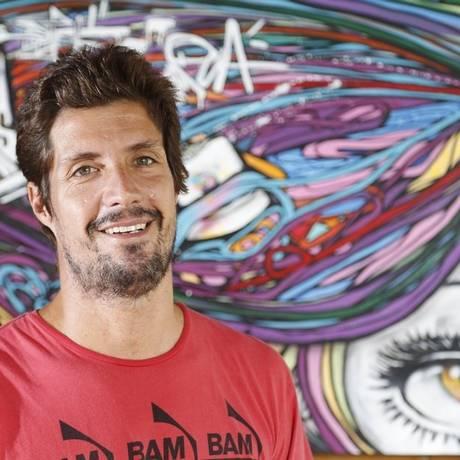 Rafael Lacerda diante de um quadro de Marcelo Ment Foto: Fabio Rossi/ Agência O Globo
