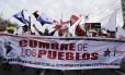 """Na Cidade do Panamá, manifestantes protestam e gritam palavras de ordem segurando uma faixa: """"Cúpula dos Povos"""""""