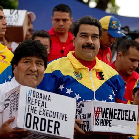 Presidente venezuelano, Nicolás Maduro (direita) ao lado do presidente boliviano Evo Morales, em ato de recolhimento de assinaturas contra a medida executiva de Barack Obama, em Caracas Foto: Fernando Llano / AP