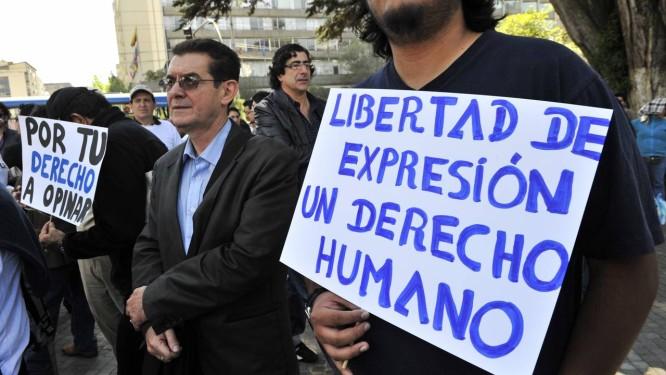 Manifestantes carregam cartazes em defesa da liberdade de imprensa durante ato em Quito, no Equador Foto: RODRIGO BUENDIA / AFP