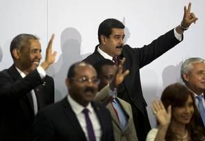 """Nos fundos da sala da Cúpula das Américas, Barack Obama acena e Nicolás Maduro faz o """"V"""" de vitória Foto: Moises Castillo / AP"""