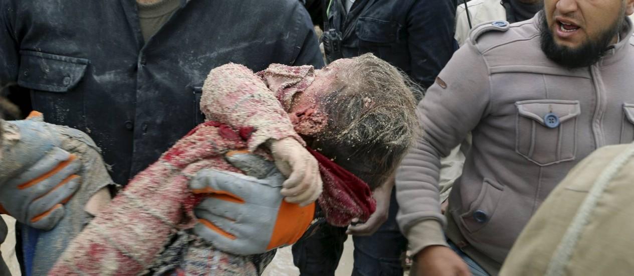 Membros da Defesa Civil carregam uma criança morta no ataque à escola Foto: ABDALRHMAN ISMAIL / REUTERS