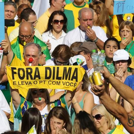 Manifestantes carregam cartazes contra o governo e o PT em protesto na Avenida Paulista, em SP Foto: Agência O Globo / Michel Filho/12-04-2015