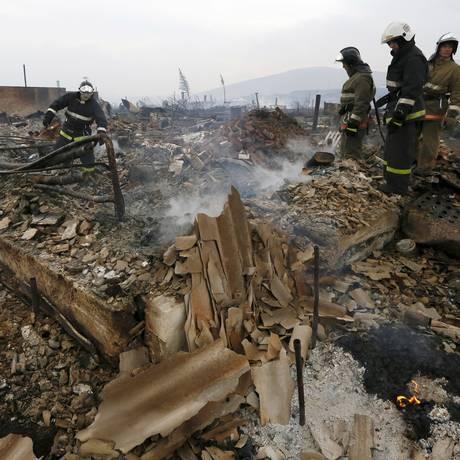 Bombeiros buscam o corpo de idosa, em meio aos escombros de uma casa destruída pelos incêndios florestais em Shyra, na região da Khakassia Foto: ILYA NAYMUSHIN / REUTERS