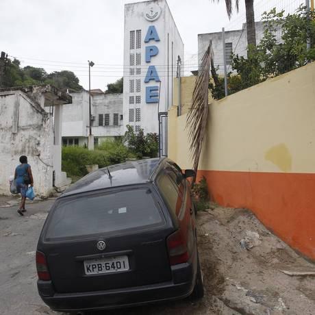 Em frente à Apae, no Centro da cidade, só se anda pela rua, pois o espaço que poderia ser uma calçada está bloqueado por um monte de concreto, sobre o qual um carro ainda estaciona Foto: Pedro Teixeira / Agência O Globo