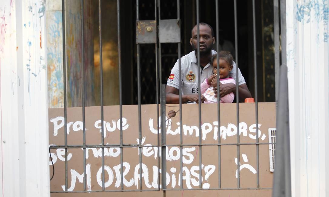 Com menina no colo, homem aguarda a polícia dentro de prédio Foto: Thiago Lontra / O Globo