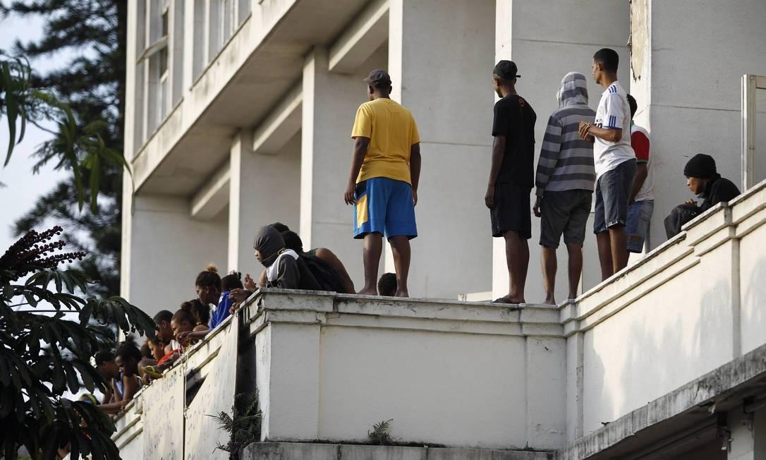 Invasores olham os carros da polícia posicionados à frente do prédio no Flamengo Foto: Thiago Lontra / O Globo