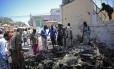 Grupo de pessoas olha os destroços de um carro-bomba do lado de fora do Ministério da Educação, em Mogadíscio