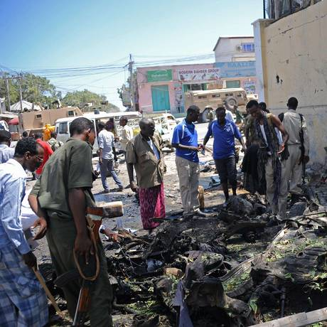 Grupo de pessoas olha os destroços de um carro-bomba do lado de fora do Ministério da Educação, em Mogadíscio Foto: Mohamed Abdiwahab / AFP