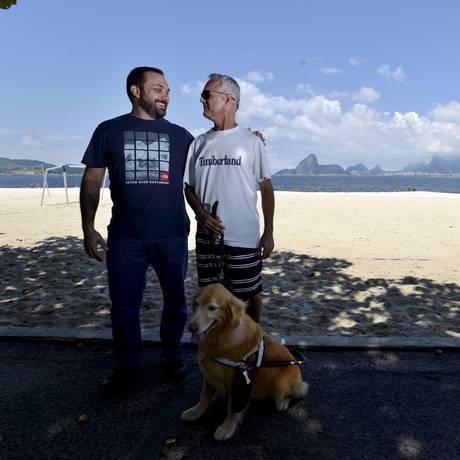 O adestrador George Thomaz Harrison com Jonas Santiago e a golden retriever Zuca Foto: José Pedro Monteiro / Agência O Globo