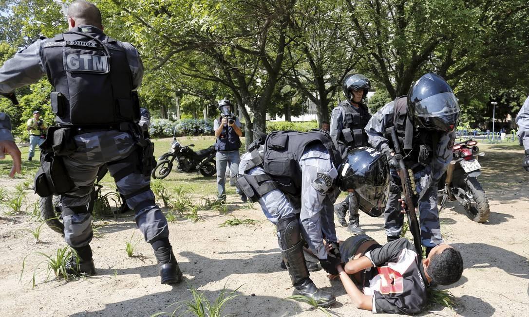 Policiais imobilizam invasor em frente ao prédio na Avenida Rui da Barbosa, no Flamengo, durante a desocupação do imóvel Foto: Pablo Jacob / O Globo