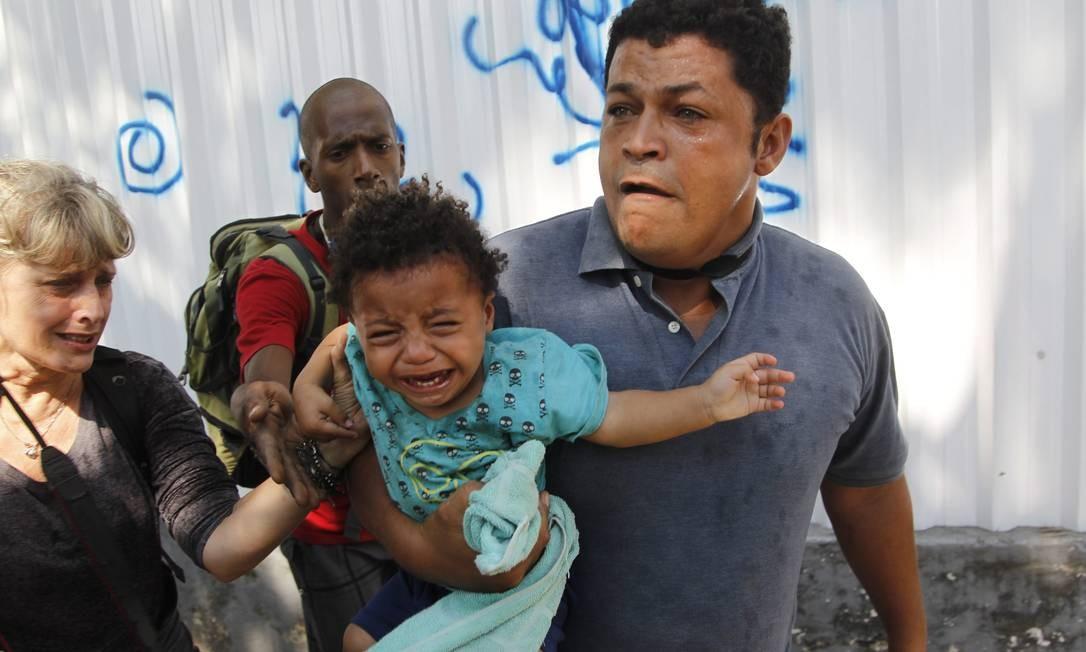 Criança chora no colo de homem retirado do prédio Foto: Marcelo Carnaval / O Globo