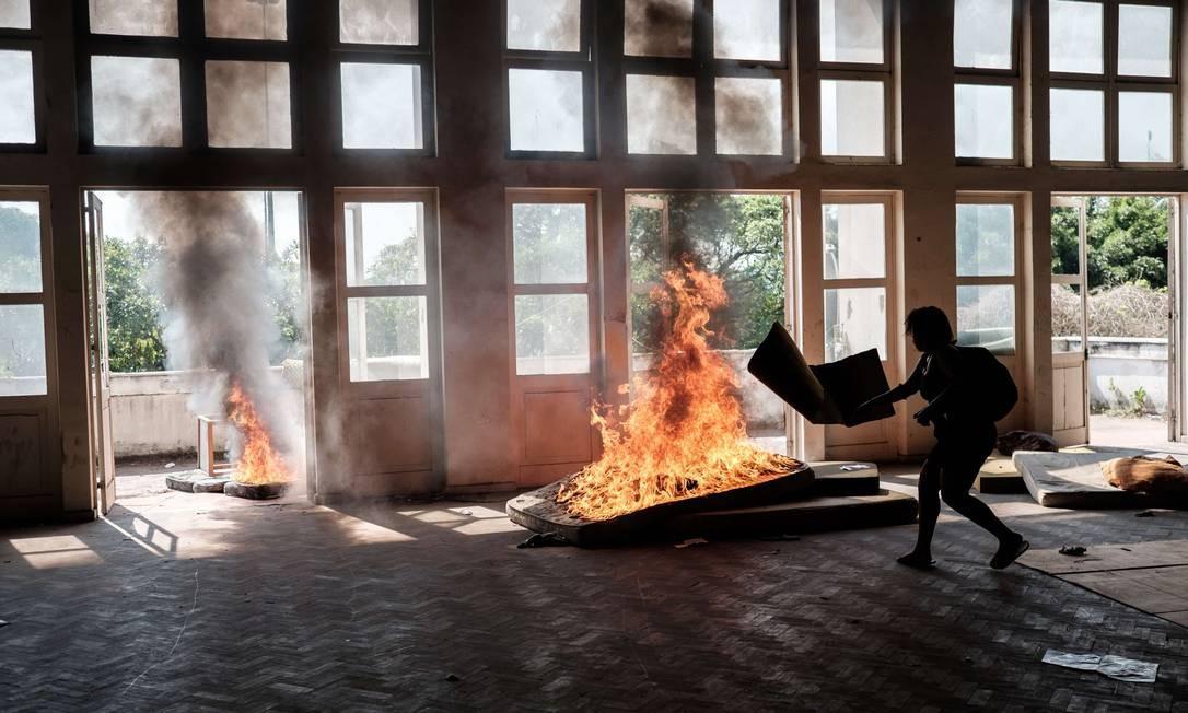 Invasores ateiam fogo em colchões depois da desocupação do edifício Foto: YASUYOSHI CHIBA / AFP