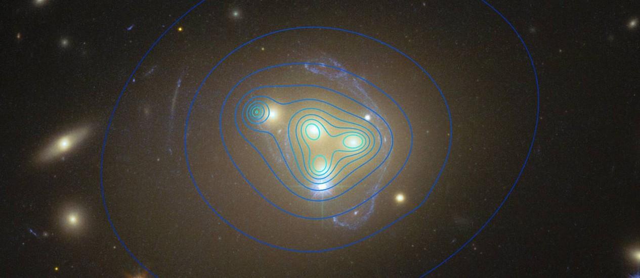 Imagem do telescópio espacial Hubble mostra a colisão de quatro galáxias no aglomerado Abell 3827 usdada no estudo, com as linhas azuis representando as concentrações de matéria escura no sistema: bolsão de matéria escura onde a galáxia mais à esquerda deveria esar inserida na verdade encontra-se desalinhada com ela, numa indicação de que foi freada pelo choque Foto: Nasa/ESA/Hubble/ESO/Richard Massey