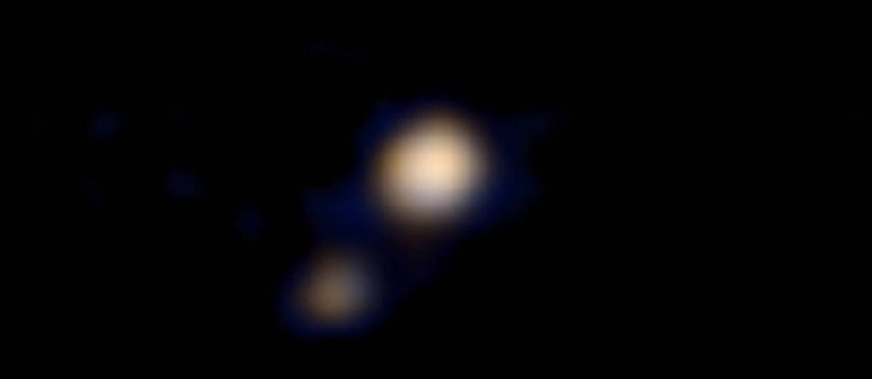 Primeira imagem a cores de Plutão e sua lua Caronte feita pela sonda New Horizons não mostra muitos detalhes, mas é prévia de importantes descobertas que a Nasa pretende fazer com a missão Foto: Nasa