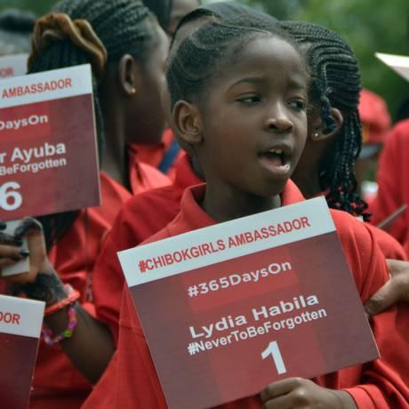 Um ano depois. Com cartazes, meninas pedem a libertação das 219 alunas raptadas por Boko Haram, na Nigéria Foto: - / AFP