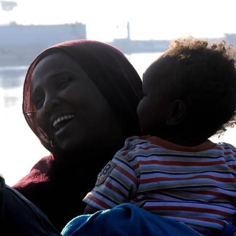 Uma imigrante carrega seu bebê depois de desembarcar de um navio da Guarda Costeira italiana no porto de Palermo, na Sicília Foto: Alessandro Fucarini / AP