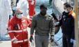 Imigrante desembarca no porto de Palermo, na Sicília, após ser resgatado pela guarda costeira italiana