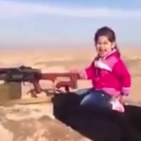 Infância roubada: menina curda brinca com metralhadora Foto: Reprodução/YPG