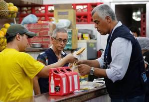 Na Cantina Sierra, um funcionário entrega um pastel a um fiscal: local foi interditado Foto: Domingos Peixoto / Agência O Globo