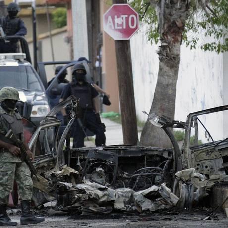 Um soldado e um policial observam os destroços de um carro-bomba que explodiu em frente a rede de TV Televisa, em Cidade Vitória, no estado de Tamaulipas, México. Foto: REUTERS/27-8-2010