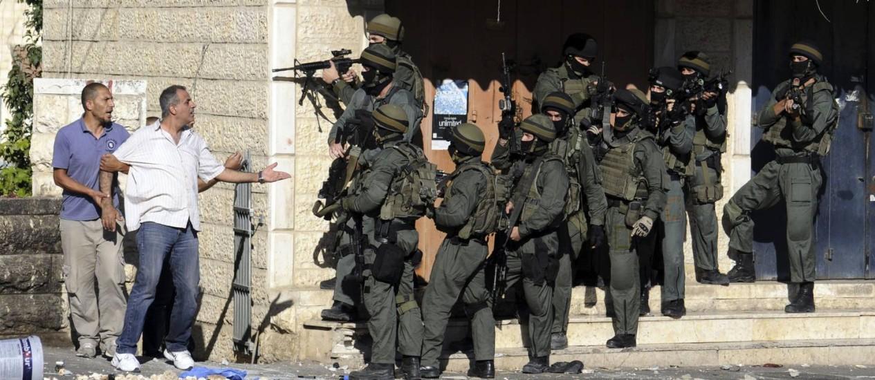 Palestino discute com polícia de fronteira em Jerusalém Oriental. Israel anunciou flexibilização das restrições para médicos da Cisjordânia que trabalham em território israelense Foto: Mahmoud Illean / AP