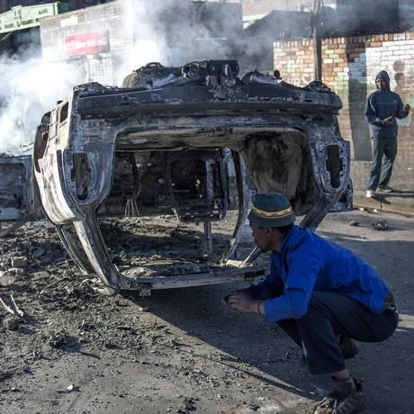 Carros são incendiados na área de Jeppestown, em Johannesburgo Foto: MUJAHID SAFODIEN / AFP