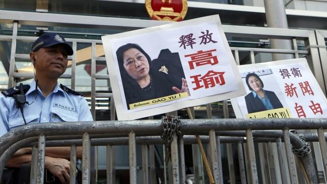 Manifestantes levaram cartazes com fotos da jornalista Gao Yu até a sede do governo em Hong Kong, em protesto por sua condenação Foto: Kin Cheung / AP