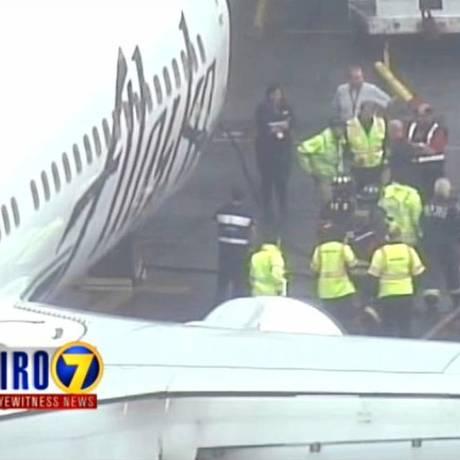 Imagem da TV mostram o funcionário que dormiu no compartimento de carga sendo removido do avião da Alaska Airlines Foto: AP/13-4-2015