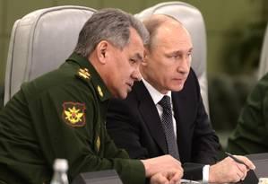 O presidente russo Vladimir Putin (direita) conversa com o Ministro da Defesa Sergei Shoigu, em visita ao Centro de Controle da Defesa Nacional Foto: Alexei Nikolsky / AP